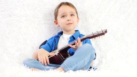A child plays a child`s acoustic guitar with pleasure while sitting on a white sofa stock video footage