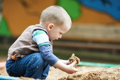 Child plays with sand Stock Photo