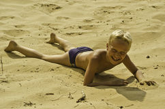 A child plays on sand. Royalty Free Stock Image
