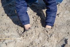 A child plays in the sand Stock Images