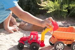 A child plays in the sand with big toy cars, an excavator, a truck Stock Images