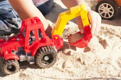 A child plays in the sand with big toy cars, an excavator, a truck Stock Photography