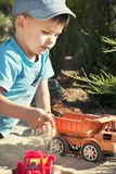 A child plays in the sand with big toy cars, an excavator, a truck Stock Image
