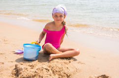 Child plays in the sand shovel and bucket on the sea shore Royalty Free Stock Photos