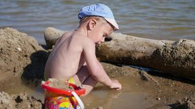 A child plays with sand and toys on the beach on a sunny hot day. Entertainment and outdoor games stock video