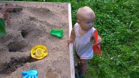 The child plays on the sandbox stock video