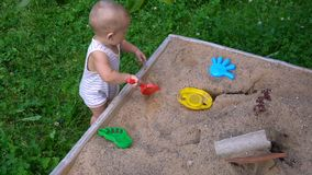 The child plays in the sandbox stock video footage