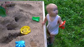 The child plays in the sandbox hd stock video footage