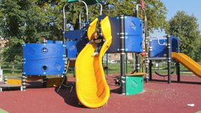Child plays on slide in an outdoor playground. Little chld having fun in an outdoor playground