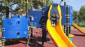 Child plays on slide in an outdoor playground stock video footage