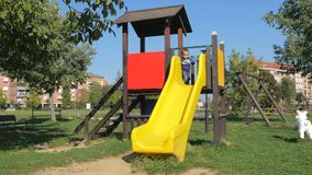 Child plays on slide in an outdoor playground stock video