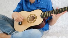 A child plays a small guitar close up. Playing the guitar, singing, music, education, rhythm. stock video footage