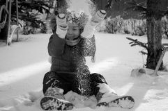 A child plays in the snow. Black and white photo of a child plays and throws snow over the head stock image