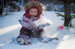 A child plays in the snow. Happy child sit and throws snow stock image