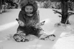 A child plays in the snow. Happy child is sitting on the snow throws stock photography
