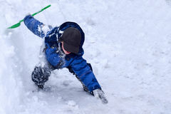 The child plays a snow ninja, the boy jumped from the snowdrift Royalty Free Stock Image