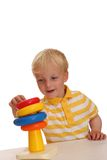 Child plays with stacking toy Stock Photos