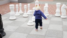 The child plays. In the street with figures of huge chess stock video