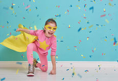 Child plays superhero. Little child plays superhero. Kid on the background of bright blue wall. Girl is throwing confetti. Yellow, pink and  turquoise colors Royalty Free Stock Image