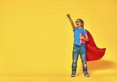 Child plays superhero. Little child plays superhero. Kid on the background of bright color wall. Education and success concept. Yellow, red and  blue Stock Photo
