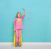 Child plays superhero. Little child plays superhero. Kid measures the growth on the background of bright blue wall. Girl power concept. Yellow, pink and Stock Photos