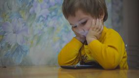 The child plays with the tablet sitting at the table. close up stock video
