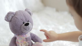 The child plays with a teddy bear stock video footage