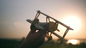 A child is playing with a toy airplane at sunset. Silhouette of a boy holding a toy, hand holding a small airplane. The. Child plays with a toy airplane in the stock video