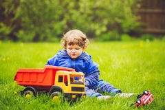 A child plays a toy car on the grass in the garden. Stock Images
