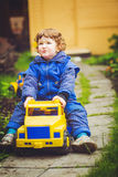 A child plays a toy car on the park. Stock Photo