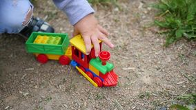 A child plays with a toy train on the sand. Outdoor games. A child plays with a toy train on the sand, close-up stock footage