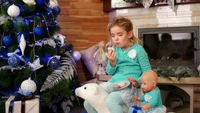 Child plays with toys, happy baby having fun eating Cake macaron, cute little girl feeding toy Pups Christmas cookies stock video footage
