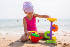 Child plays with toys in the sand on the beach Royalty Free Stock Image