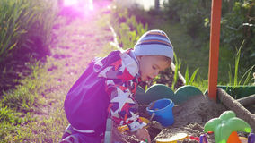 The child plays with the toys in the sandbox.Summer Sunny day. Fun and games outdoors Royalty Free Stock Photos