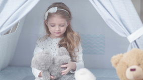 A child plays with toys, talking with them and embraces a soft toy. stock footage