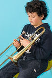 Child plays the trombone. Stock Images
