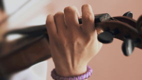 Child plays on a violin. close-up