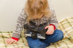 The child at home with virtual reality glasses. The child plays with VR glasses Royalty Free Stock Images