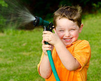 Child plays with water hose outdoors royalty free stock images