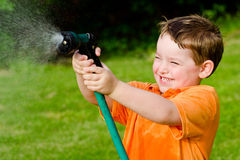 Child plays with water hose outdoors Stock Image