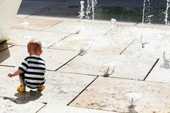 Child Plays With Water Jets Stock Photos