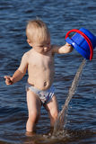 Child plays with water on the river Stock Image