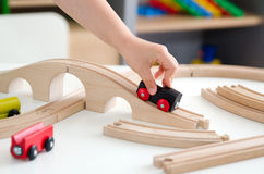 Child plays with a wooden toy train. Toy wooden train toys education white background wood concept Stock Photography