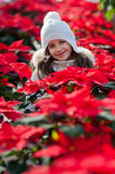 Child with poinsettias. Little girl with white cap between poinsettias royalty free stock photography