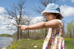 Child Pointing At The Beach. Four year old girl is at a small beach and pointing at the water Royalty Free Stock Images