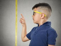 Child pointing at his height on measuring tape Royalty Free Stock Image