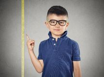 Child pointing at his height on measuring tape. I'm growing up. Child with glasses pointing at his height on measuring tape beside him, grey wall background royalty free stock image