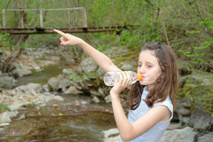 Child pointing in the nature while drinking water Stock Image