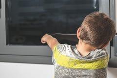 Child pointing through a window stock photo