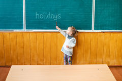 Child points to a school board Royalty Free Stock Photos